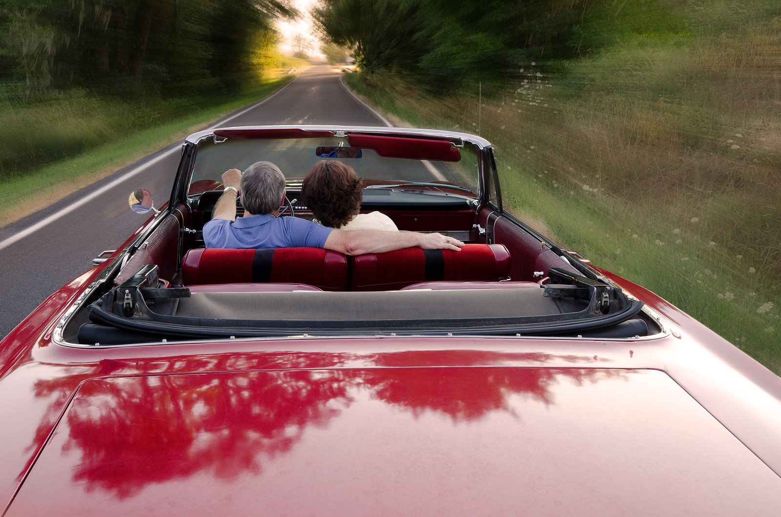 A couple rides in a convertible on a summer evening.